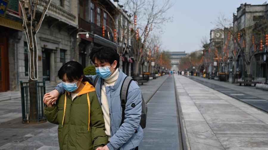 6mar2020---casal-usando-mascaras-anda-em-rua-comercial-de-pequim-china-reportou-mais-30-mortes-por-covid-19-nesta-sexta-feira-6-1583487442126_v2_900x506